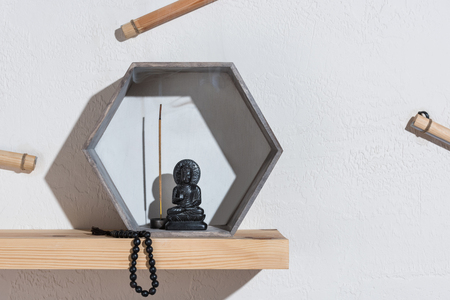 small statue of buddha in frame and rosary