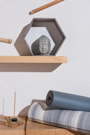 buddha head in frame and yoga mats with incense sticks