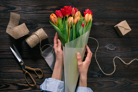 woman wrapping bouquet of tulips into wrapping paper on wooden tabletop Stock Photo