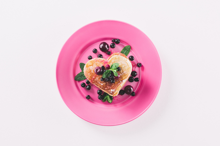 top view of heart shaped pancake with berries and mint isolated on white