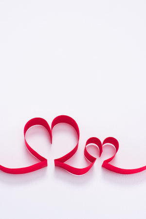 two red hearts from ribbon on white Stock Photo