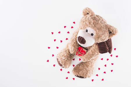 top view of teddy bear with heart shaped gift box and paper hearts