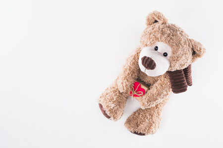 top view of teddy bear with heart shaped gift box isolated on white