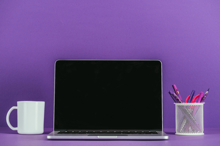 workplace with laptop and coffee mug on purple surface Stock Photo