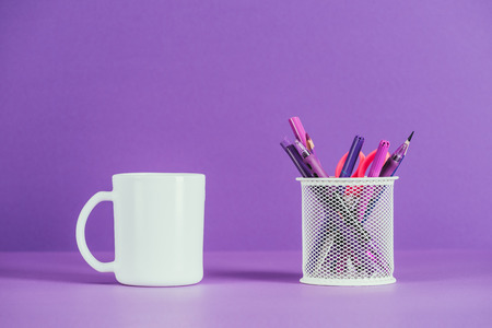 cup and pen holder on purple surface Stock Photo