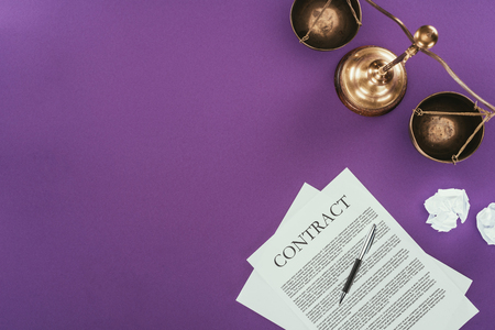 top view of business contract with pen and justice scales on purple surface