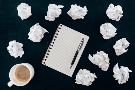 top view of blank notepad with messy crumpled papers and cup of coffee isolated on black