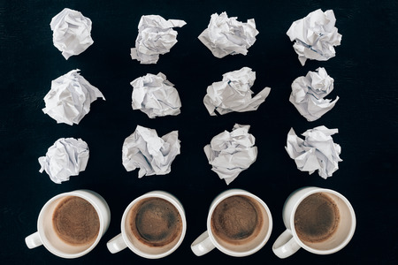 top view of crumpled papers and cups of coffee in rows isolated on black