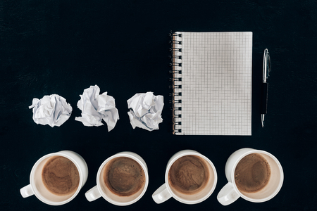top view of blank notepad with crumpled papers and cups of coffee in row isolated on black