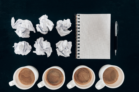 top view of blank notebook with crumpled papers and cups of coffee in row isolated on black