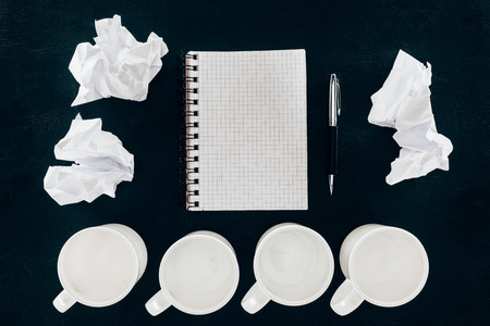 top view of blank notepad with crumpled papers and empty cups in row isolated on black Imagens