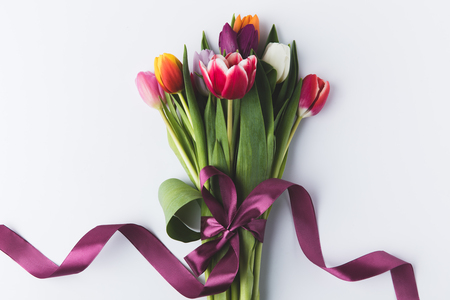 beautiful colorful tulips with purple ribbon isolated on grey 스톡 콘텐츠