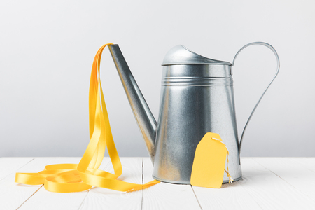 close-up view of shiny watering can with yellow ribbon and blank label on grey Stock Photo