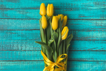 top view of beautiful yellow tulip flowers with ribbon on turquoise wooden surface
