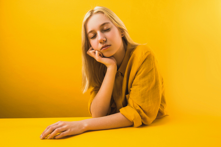 young woman in yellow clothing sitting with closed eyes on yellow Imagens
