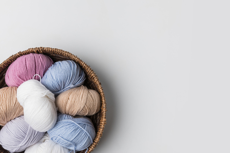 top view of colored yarn balls in wicker basket on white background Stok Fotoğraf - 95331483