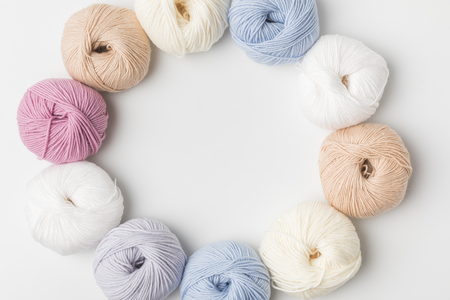 top view of circle of colored yarn balls on white background