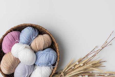 白い背景にウィッカーバスケットと乾燥植物の色の糸ボールのトップビュー 写真素材