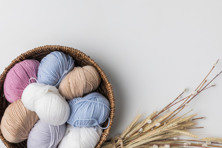top view of colored yarn balls in wicker basket and dried plants on white background