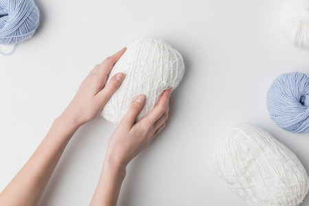 cropped view of woman holding white yarn ball in hands on white background