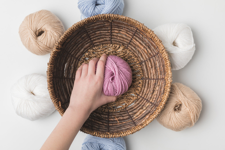 cropped view of woman holding pink yarn ball in hand in wicker basket on white background