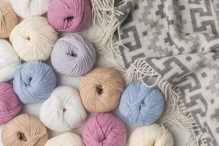 scattered colored yarn balls and blanket  on white background  Archivio Fotografico