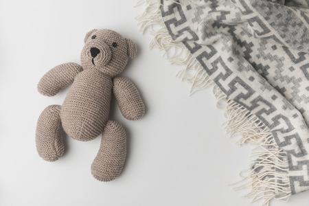 top view of teddy bear  laying near blanket on white background