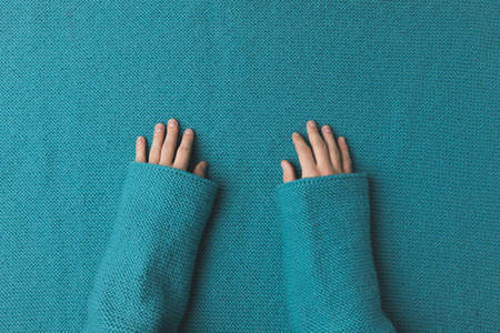 cropped view of woman hands laying over turquoise fabric