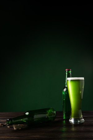 glass bottles and glass of green beer on table, st patricks day concept Stok Fotoğraf - 95331180