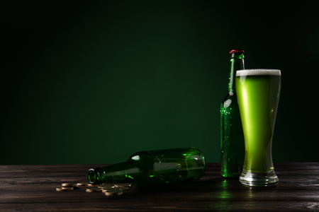 glass bottles and glass of green beer on wooden table, st patricks day concept Stok Fotoğraf - 95331184