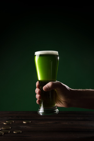 cropped image of man holding glass of green beer above table with coins, st patricks day concept Stok Fotoğraf - 95331197