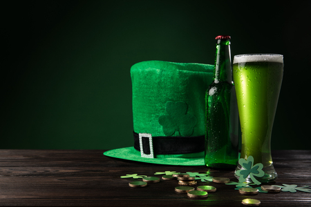 green hat with green beer and coins on wooden table, st patricks day concept