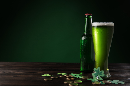 glass bottle and glass of green beer with coins on wooden table, st patricks day concept