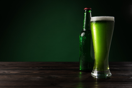 glass of green beer with bottle on wooden table, st patricks day concept Stok Fotoğraf - 95331214