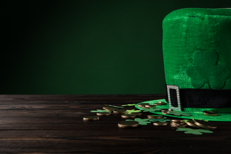 green hat with golden coins and shamrock on wooden table, st patricks day concept Stok Fotoğraf