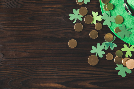 top view of green hat with golden coins and shamrock on wooden table, st patricks day concept