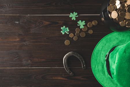 top view of pot with golden coins, horseshoe and green hat on wooden table, st patricks day concept 스톡 콘텐츠