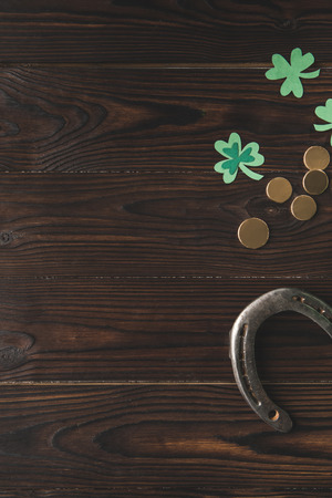 top view of golden coins, horseshoe and shamrock on wooden table, st patricks day concept