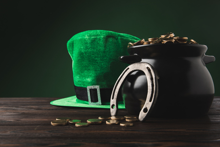 pot with golden coins, horseshoe and green hat on table, st patricks day concept
