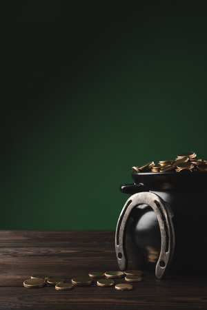 pot with golden coins and horseshoe on table, st patricks day concept Stok Fotoğraf - 95331114