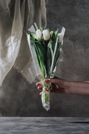 cropped view of woman holding bouquet of tulips in cellophane on grey surface