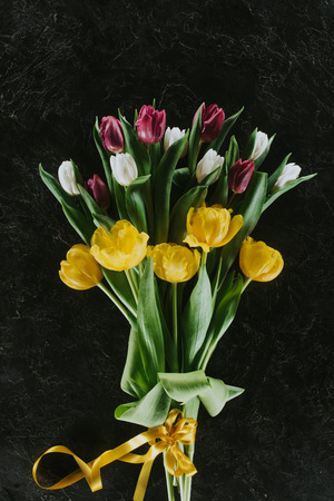 top view of bouquet with tulips on black surface for 8 march Banco de Imagens - 95330910