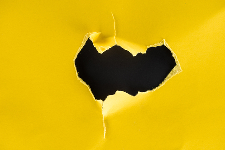 close-up shot of hole in yellow paper isolated on black Фото со стока - 95330791