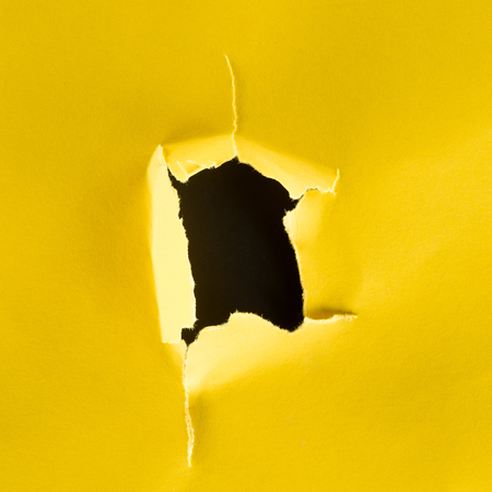close-up shot of hole in yellow paper isolated on black
