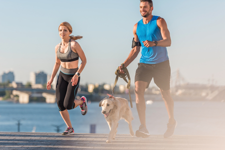 sportswoman and sportsman jogging with dog