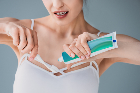 Woman squeezing toothpaste on brush