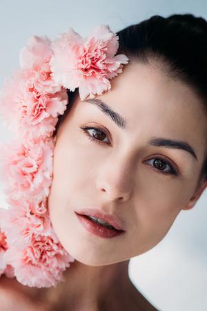 ピンクのクローブの束を持つ魅力的な女性