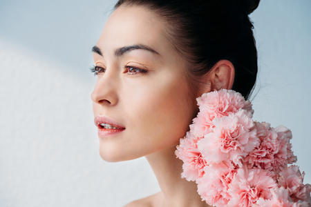 新鮮な肌とピンクのクローブを持つ女性