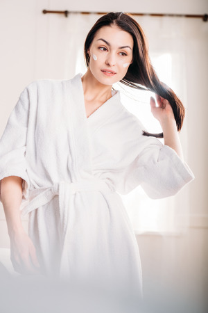 woman in bathrobe with cream on face Stock fotó - 95487419