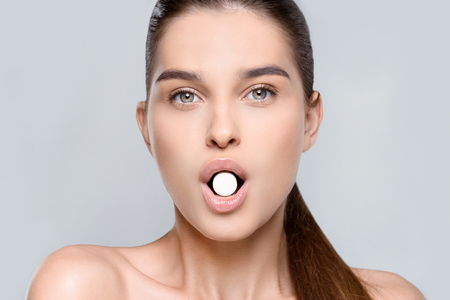 woman holding white pill